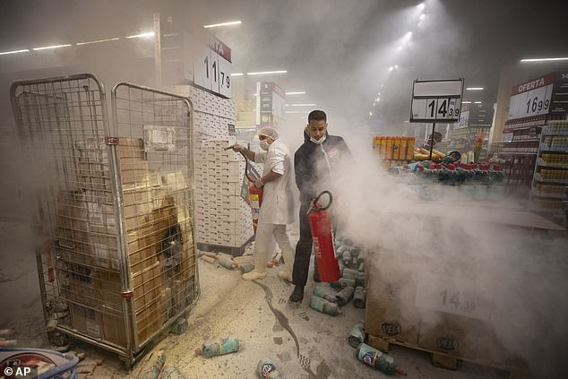 Employees douse a fire set by protesters inside a Carrefour supermarket during a protest against the murder of Black man Joao Alberto Silveira Freitas
