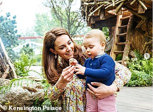 In the photo, Kate crouches down to cuddle her toddler son as he explores the garden