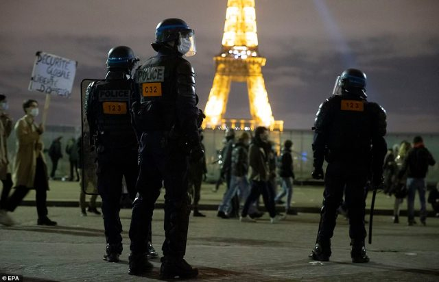 Riot police clear protesters gathered on Place du Trocadero near the Eiffel Tower after a demonstration against the controversial global security law in Paris