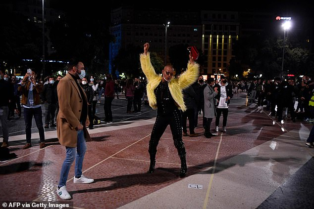 Catalonia is set to reopen bars, cinemas and restaurants on Monday after a month-long lockdown forced them to close. Pictured: A reveller dancing on the street tonight