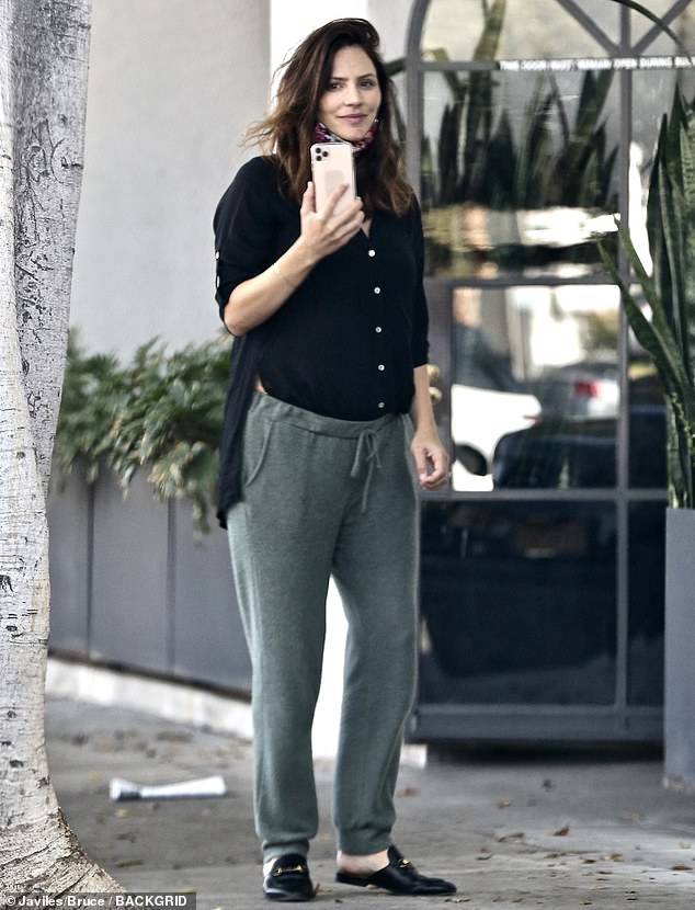 Katharine McPhee covers her baby bump in a black shirt as she stops to take a phone call in LA