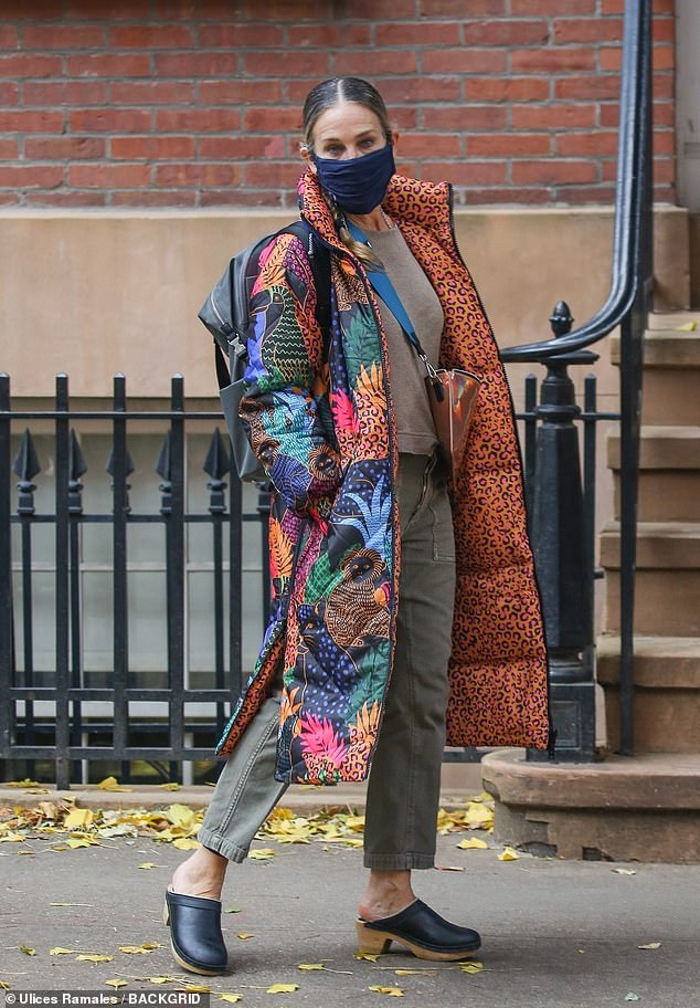 Sarah Jessica Parker strikes a pose on the NYC sidewalk in her colorful jungle patterned puffer coat