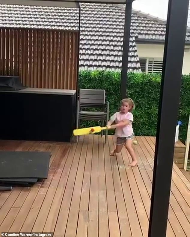 Too cute: David, 34, shared two adorable videos to Instagram of Candice coaching their children who looked eager to learn.Little Indi Rae (pictured) looked cute as a button as she batted with all her might, after Candice threw the ball into the air