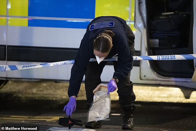 A police crime scene investigator puts a glove in an evidence bag on Queen Street in Cardiff