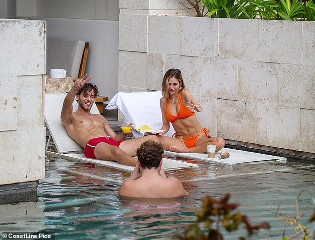 Three's not a crowd:The two were joined by a male pal, who happily snapped photos of the lovebirds as they cooled off in the pool and sipped on coffee and orange juice
