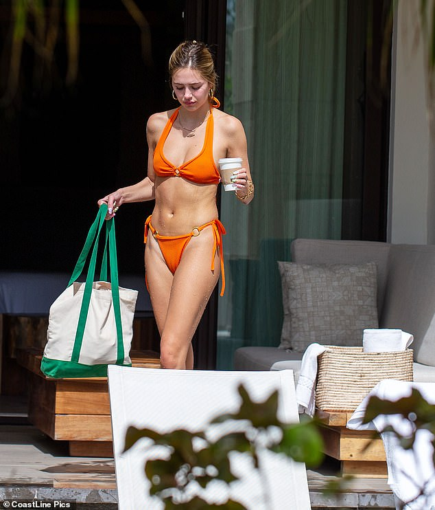 Ready for the day: Delilah looked gorgeous in her bikini as she headed to the pool with a coffee and her beach bag in hand