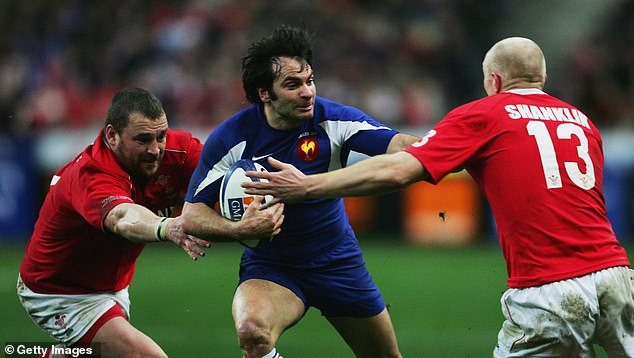 Dominici fends off Welsh tackles in a Six Nations clash at Stade de France in 2007