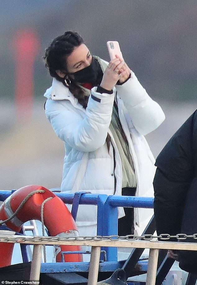 On location:Michelle put safety first with a black face mask as she appeared to take several shots of the scenic river views