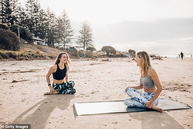 The northern NSW town has become the wellbeing capital of Australia, with keen yogis and health fans often spotted working out on the beach (pictured)