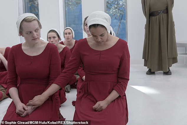 The original novel has been made into a popular TV series, which was met with critical acclaim when it debuted in 2017, pictured,Elisabeth Moss as handmaid Offred