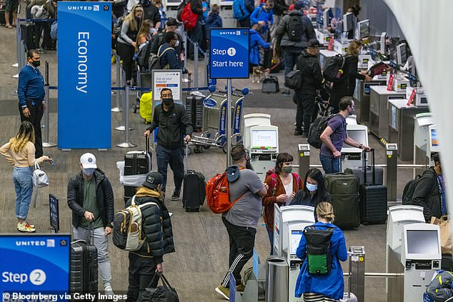 Travelers wearing protective masks check in at a United Airlines deskat San Francisco International Airport on Tuesday despite the rising coronavirus cases in the state
