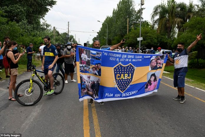 TIGRE, ARGENTINA - NOVEMBER 25: Fans of Boca Juniors hold a banner as they gather outside the home of Diego Maradona at San Andres neighbourhood on November 25, 2020 in Tigre, Argentina