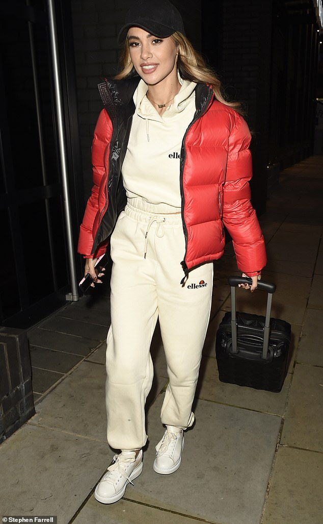 A hard day's work:The reality star embraced the chilly November weather as she sported a red quilted jacket while pulling a suitcase through the city and holding her mobile phone