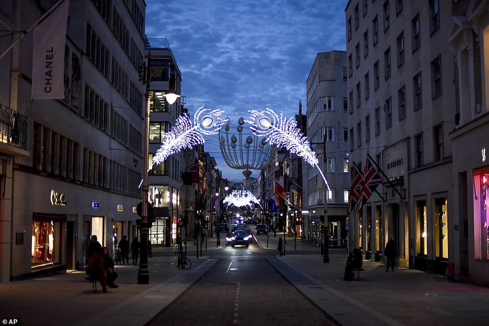Are we being softened up? Is Boris, having posed as a genial Father Christmas, about to revert to Scrooge? Pictured, Christmas lights on New Bond Street in Mayfair, London, on Tuesday