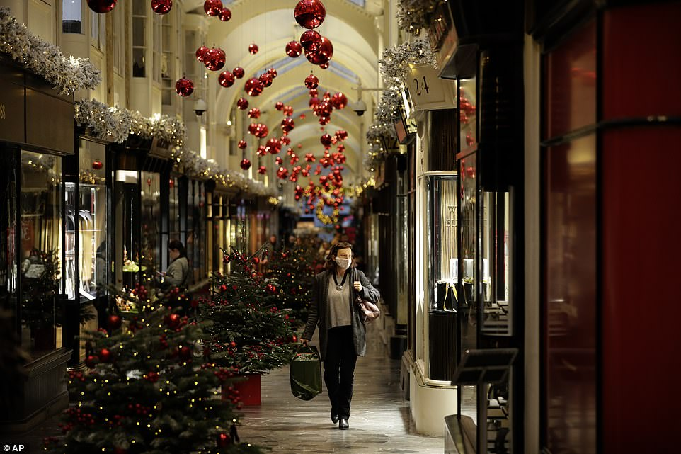 A shopper walks through central London'sBurlington Arcade on Wednesday - the capital is expected to be under Tier 2 restrictions meaning all pubs must close unless they can function as restaurants and people from separate households cannot mix indoors