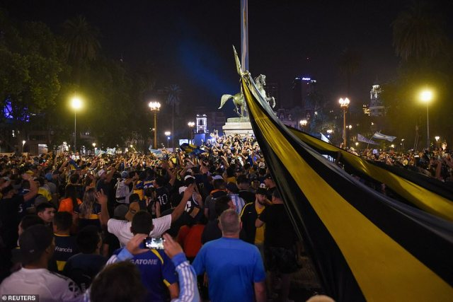 A crowd of fans - some of them wearing the colours of Argentinian team Boca Juniors where Maradona played for part of his career - gather near the presidential palace last night ahead of Maradona's wake