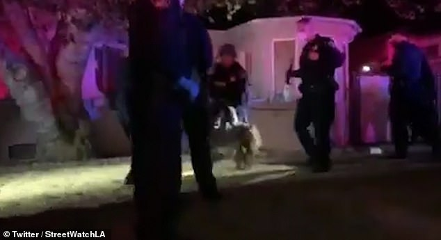 A teenager has been pinned to the ground by officers after she was forcibly removed from a house alongside her mother amid violent protests in Los Angeles