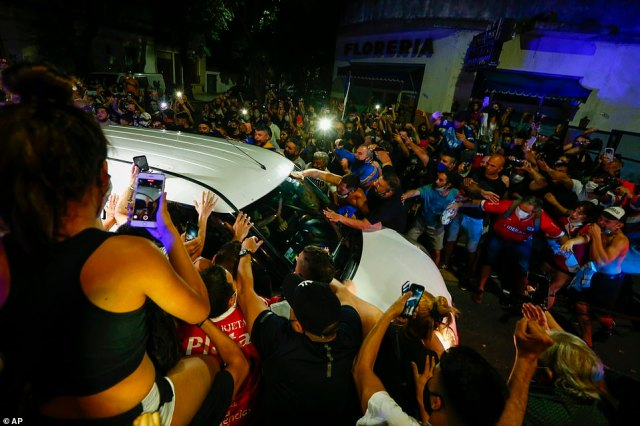 Football founds surround the hearse carrying Diego Maradona's coffin to an undertaker in Buenos Aires on Wednesday
