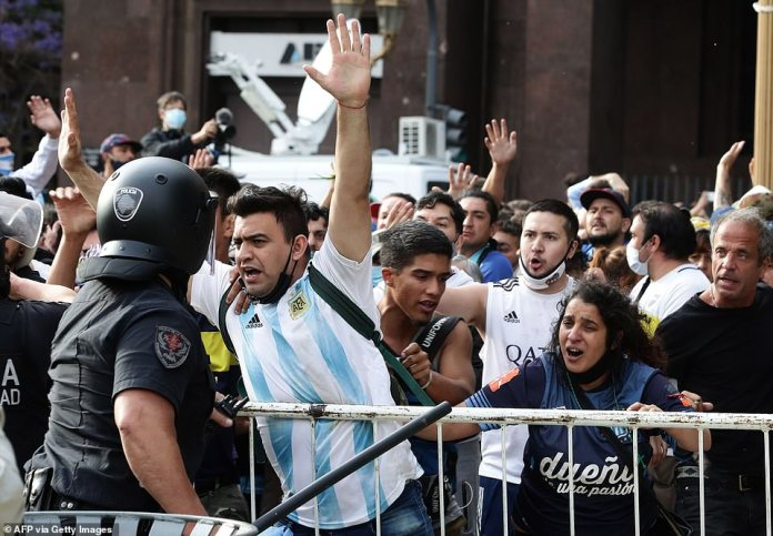 Face to face: Thousands of mourners gathered at the presidential palace in Buenos Aires to see Diego Maradona's casket today - but there were scuffles as people jostled to get inside and see their hero