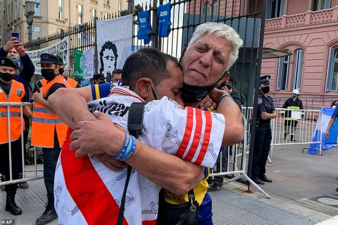 Supporters of rival Argentinian teams, River Plate and Boca Juniors, embrace as they wait to enter the presidential palace to see the coffin of a man who was revered in the country as the captain of a World Cup-winning team in 1986