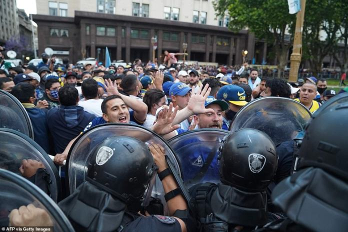 Riot police try to keep order as Maradona fans - some of them wearing the colours of his former team Boca Juniors - push to enter the presidential palace and see his coffin before his burial on Thursday