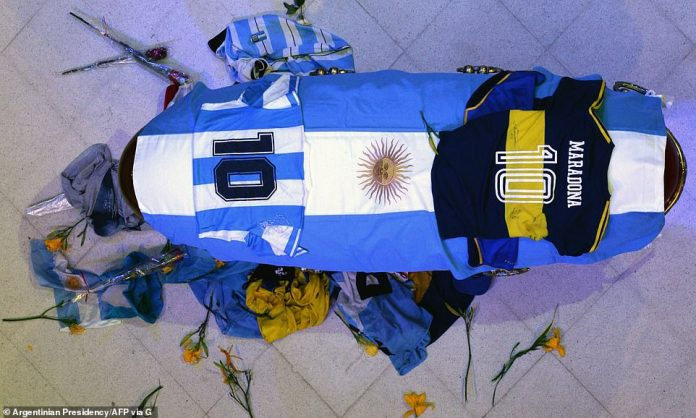 On display: Mourners left flowers, football shirts and flags at the foot of Maradona's coffin, as they filed past it at the presidential palace where it is lying in state on the first of three days of national mourning in Argentina