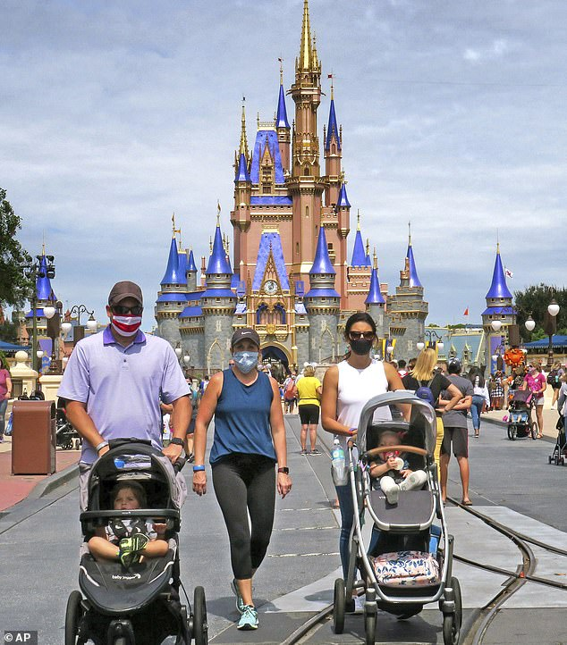 Walt Disney Co will lay off about 32,000 workers - 4,000 more than the 28,000 announced in September - as the company continues to struggle with its theme parks due to coronavirus closures and restrictions. A view of masked-up guests at Disney World in Florida in September after the park reopened during the pandemic in July