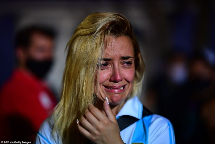 A fan wearing an Argentina shirt in tribute to Maradona cries at a gathering outside the Diego Armando Maradona Stadium in Buenos Aires where the football legend began his career as a young player