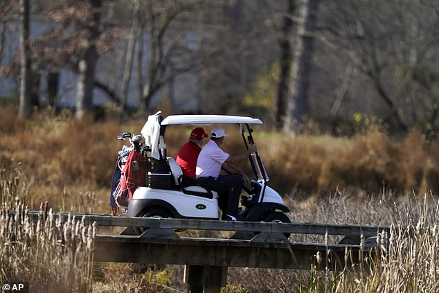 President Trump drives a golf cart on his course near Washington D.C.