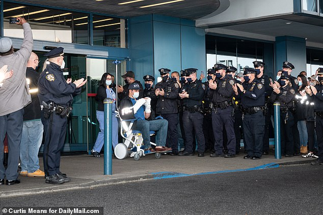 Wells is wheeled out of hospital to a hero's welcome as a police source revealed the CUNY security officer suspect who shot him and Murphy was so determined to kill his wife he allegedly stepped over him to try to get to her