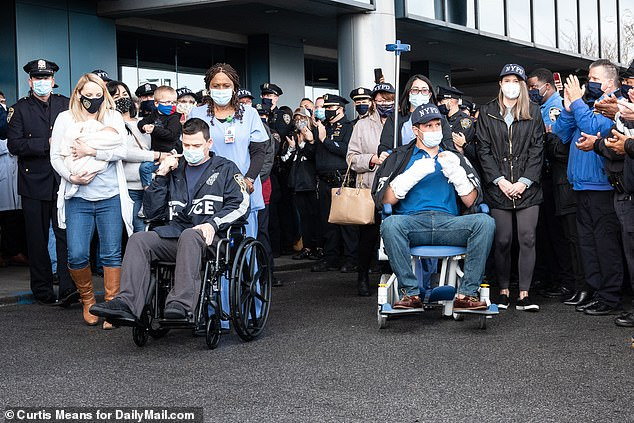 Officers Christopher Wells, 36, (left) and Joseph Murphy, 33, (right) were released from Jamaica Hospital in Queens Thursday morning to be met by a crowd of cheering police officers including NYPD Police Commissioner Dermot Shea