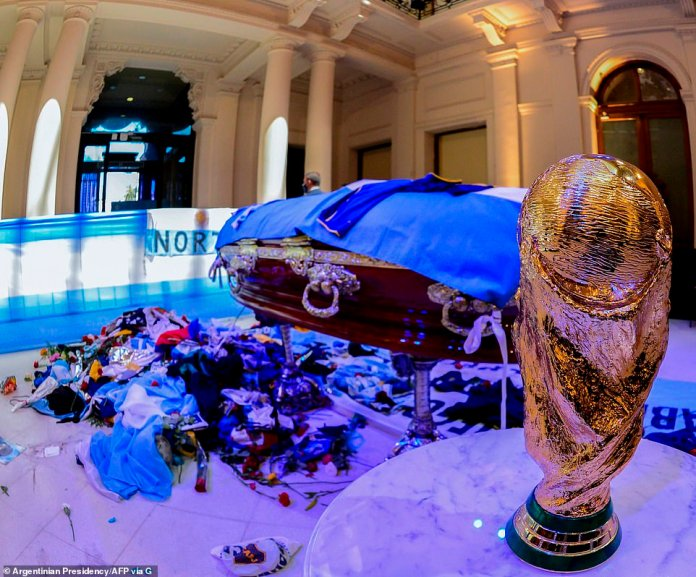 A replica of the World Cup trophy which Maradona led Argentina to in 1986 in Mexico stands beside the coffin draped in the Argentinian flag as piles of football jerseys lie on the floor of the presidential palace in Buenos Aires on Thursday