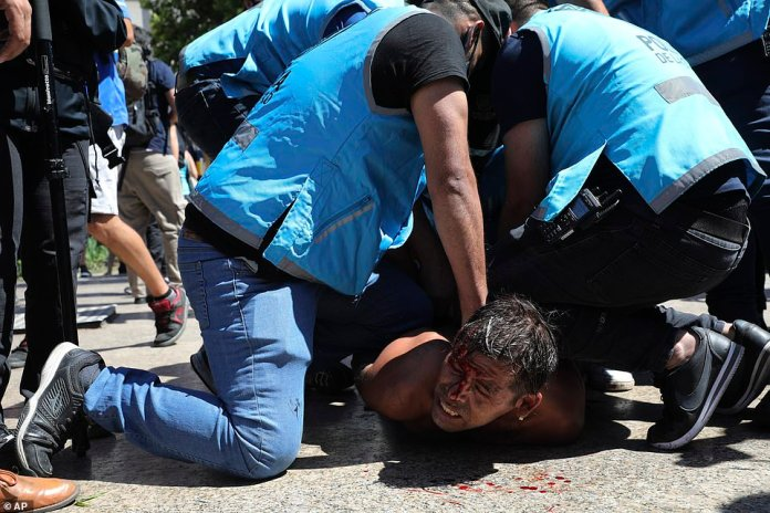 Police detain a soccer fan at Plaza de Mayo, where mourners are lining up to see the casket with the remains of Diego Maradona lying in state inside the presidential palace, in Buenos Aires
