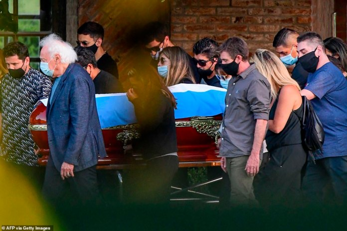 Relatives and friends carry the coffin of the late Argentine football legend Diego Armando Maradona during his funeral at the Jardin Bella Vista cemetery, in Buenos Aires province