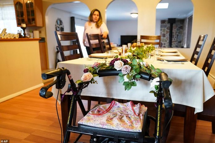 Deer Park, New York: Like thousands of Americans, Alexa Rivera recently lost a loved one this year. Rivera is seen standing at the dining room table as the walker once belonging to her recently deceased mother Ana Martinez rests beside an empty place setting before Thanksgiving dinner