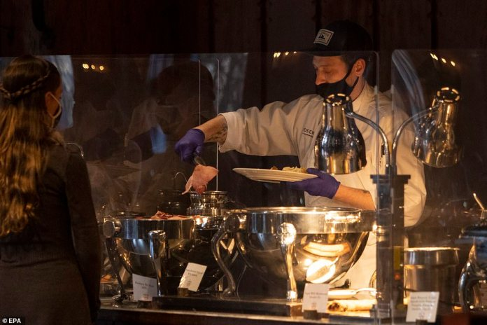 Yosemite Valley, California: A server attouch-less dinner buffet in Ahwahnee Dining Room is seen dipping food for a customer on Thursday