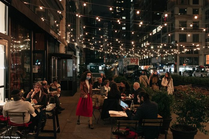 New York, New York: Families, couples, and friends dine outside at a restaurant for Thanksgiving dinner