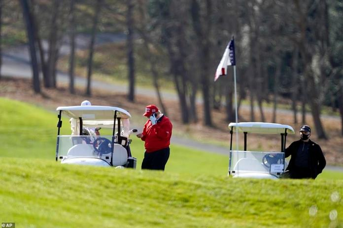 President Donald Trump holds his phone as he stands next to a golf cart on his course