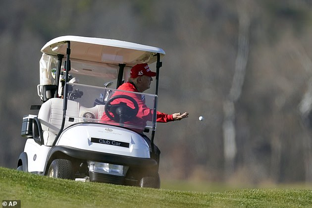 Trump is seen tossing a golf ball from his cart as he plays golf at his club in Virginia
