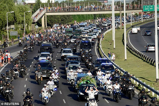 The hearse carrying his casket drives to the cemetery watched by hordes of mourners