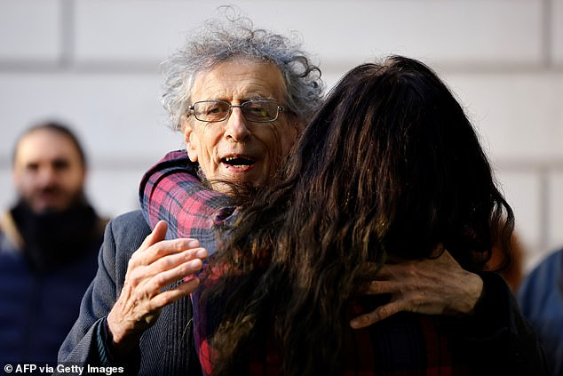 Piers Corbyn hugs a supporter outside the court as he arrives for his trial this morning