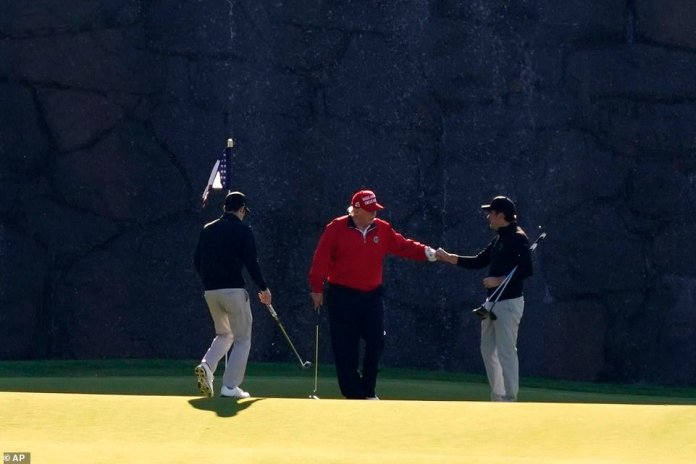 President Trump gives a fist bump to a fellow golfer
