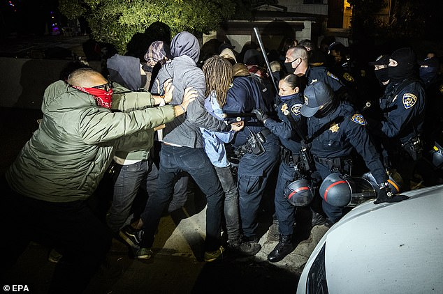 California Highway Patrol officers clash with activists reclaiming California Department of Transportation homes, as they forcefully remove them from the premises last night in El Sereno, Los Angeles