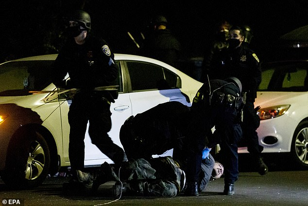 An activist is apprehended by CHP officers during the demonstration in El Sereno, Los Angeles last night