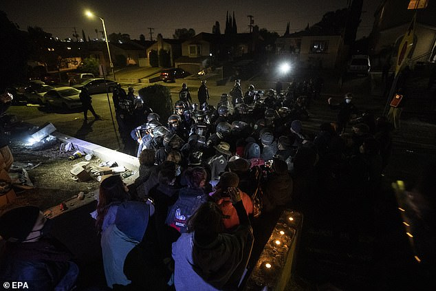 A view of the demonstration shows activists clashing with CHP officers clad in riot gear last night in El Sereno, Los Angeles