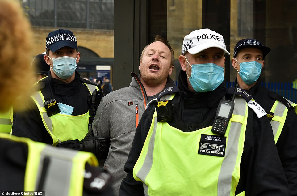 A man is carried away by police wearing facemasks at an anti-lockdown protest in London