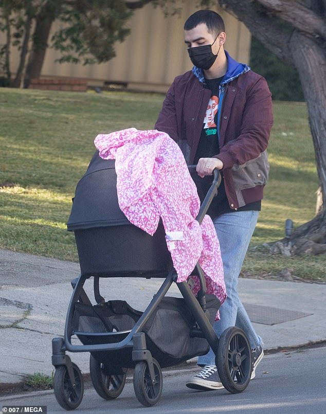 Safety first: He covered Willa up with a pink patterned blanket and wore a black mask to slow the spread of the novel coronavirus, which is surging to record numbers in Los Angeles County