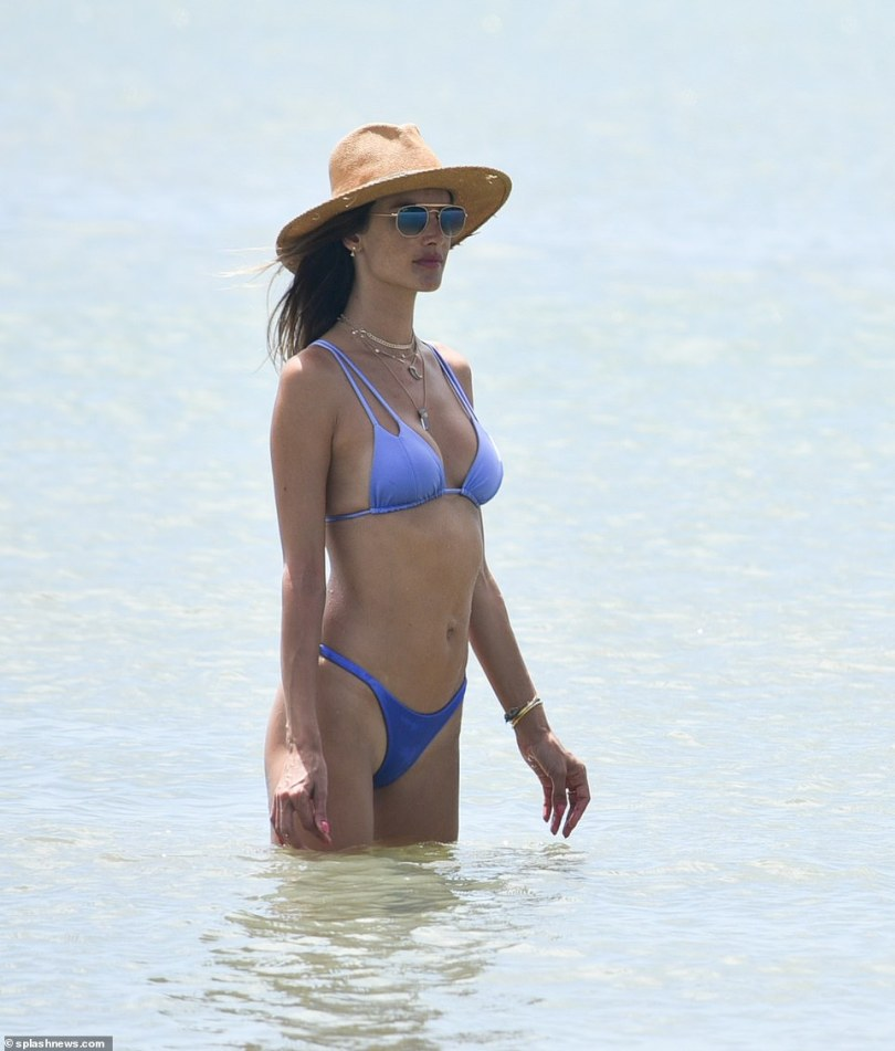 Keeping cool: She looked effortlessly chic as she rocked a straw panama hat while frolicking in the ocean