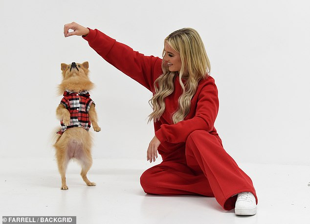Playful: The beauty, 26, looked cosy as she donned scarlet loungewear while playing with her beloved dog