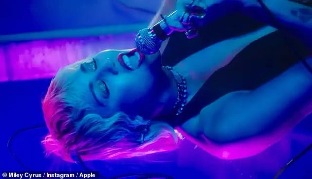 Moody: Miley utilized a corded microphone for her performance and illuminated herself with a psychedelic lighting set up that included shades of blue, pink, and purple